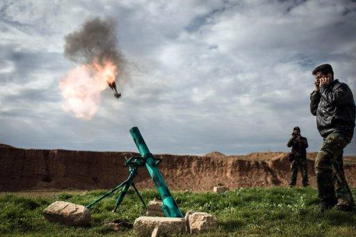 <p>Syrian rebels fire a mortar towards regime forces stationed at Kwiriss airport in Al-Bab, 30 kilometres from the northeastern Syrian city of Aleppo on February 14, 2013. Syria's army and rebels were preparing for a major battle for control of strategic airports in Aleppo, a watchdog said, four days after insurgents launched assaults on airbases in the northern province.</p>