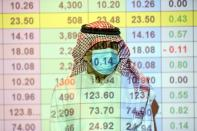 FILE PHOTO: A Saudi trader wears a mask as he monitors stock information at the Saudi stock market in Riyadh