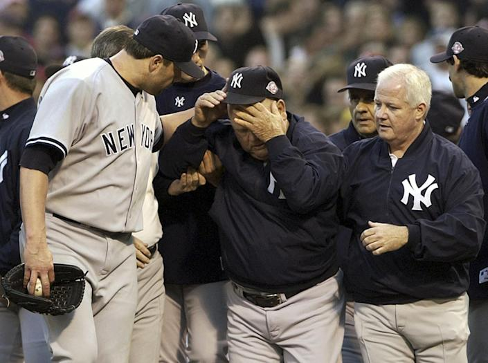 New York Yankees' Roger Clemens looks after bench coach Don Zimmer, who had been thrown to the ground by Pedro Martinez.