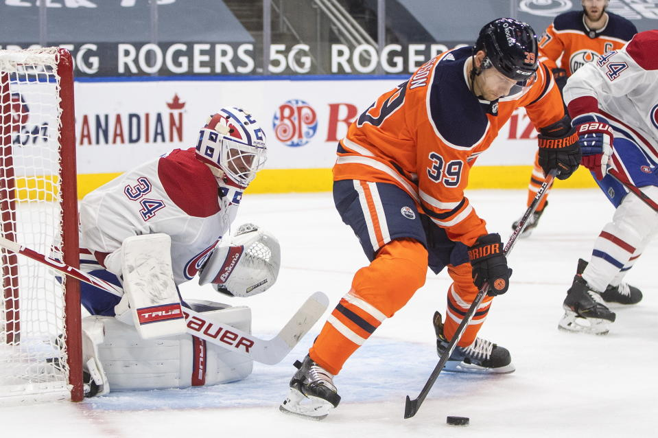 Edmonton Oilers' Alex Chiasson (39) tries to tip the puck in past Montreal Canadiens goalie Jake Allen (34) during second-period NHL hockey game action in Edmonton, Alberta, Monday, Jan. 18, 2021. (Jason Franson/The Canadian Press via AP)