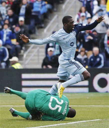 Sporting Kansas City forward C.J. Sapong leaps over Chicago Fire goalkeeper Sean Johnson (25) during the first half of an MLS soccer match in Kansas City, Kan., Saturday, March 16, 2013. Johnson made a save on the play. (AP Photo/Orlin Wagner)