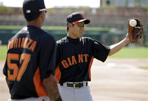 San Francisco Giants second baseman Kensuke Tanaka flips a baseball with Ehire Adrianza before an exhibition spring training baseball game against the Chicago White Sox Monday, March 4, 2013, in Glendale, Ariz. (AP Photo/Mark Duncan)
