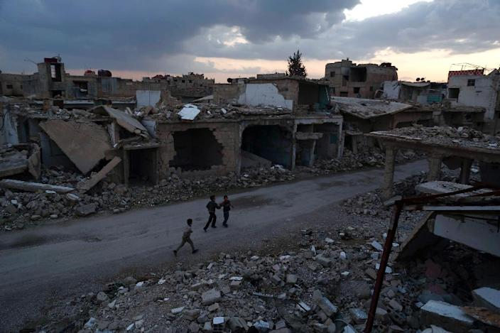 Syrian children walk past heavily damaged buildings in the rebel-held town of Douma, on the eastern edges of the capital Damascus on February 27, 2016, on the first day of the landmark ceasefire agreement (AFP Photo/Sameer Al-Doumy)