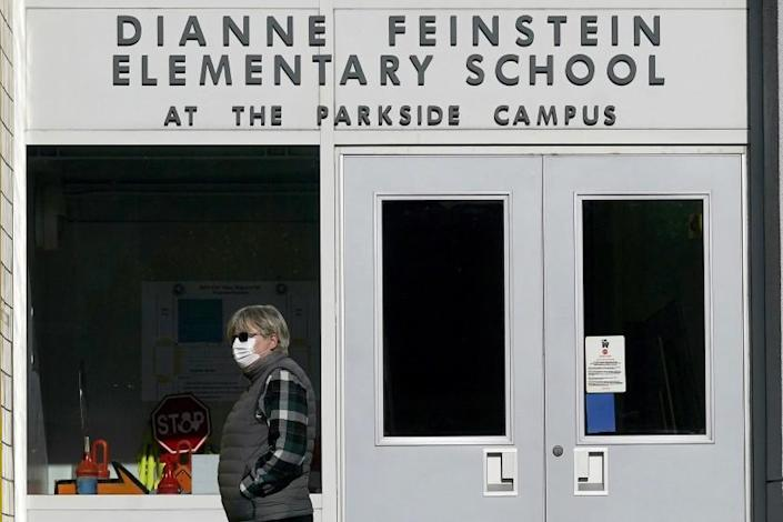 A pedestrian walks below a sign for Dianne Feinstein Elementary School in San Francisco, on Dec. 17, 2020. The San Francisco school board has voted to remove the names of George Washington and Abraham Lincoln from public schools after officials deemed them and other prominent figures, including Sen. Dianne Feinstein unworthy of the honor. After months of controversy, the board voted 6-1 Tuesday, Jan. 26, 2021, in favor of renaming 44 San Francisco school sites with new names with no connection to slavery, oppression, racism or similar criteria, the San Francisco Chronicle reported. (AP Photo/Jeff Chiu)