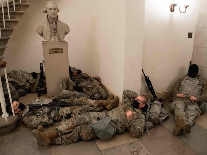 <p>Members of the National Guard take a rest in the Rotunda of the US Capitol in Washington, DC on 13 January 2021</p> ((AFP via Getty Images))