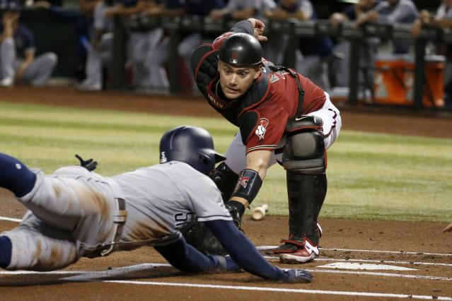 Arizona Diamondbacks catcher Carson Kelly, right, tags out San Diego Padres' Greg Garcia at home during the first inning of a baseball game Wednesday, Sept. 4, 2019, in Phoenix. (AP Photo/Ross D. Franklin)