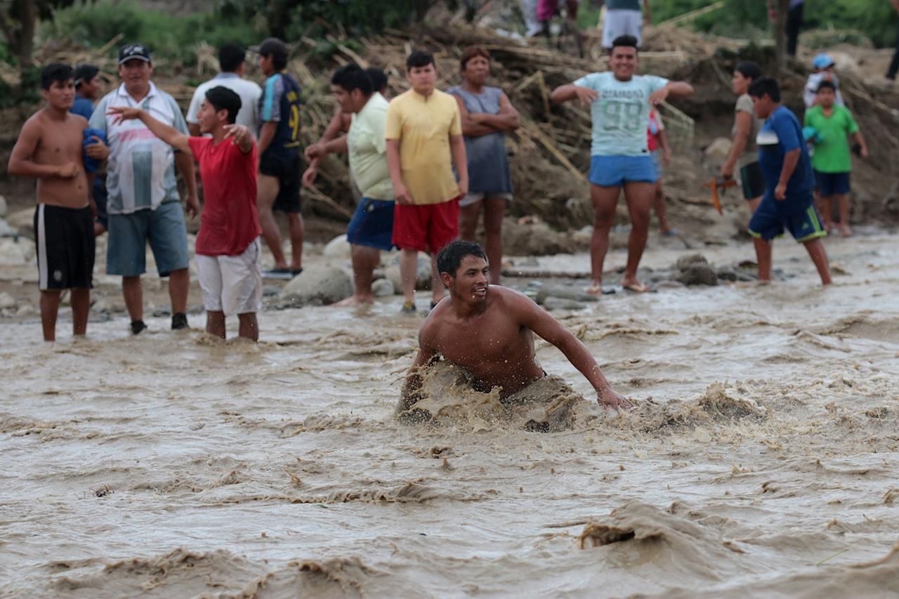 <p>Residents cross the Viru river after the Viru bridge at the Pan American highway collapsed following a massive landslide and flood in Trujillo, northern Peru, March 20, 2017. (Douglas Juarez/Reuters) </p>
