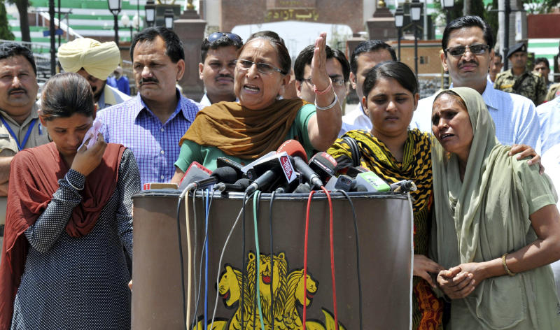 Dalbir Kaur, sister of Sarabjit Singh, an Indian spy on death row in Pakistan, addresses the media as Singh's wife Sukhpreet Kaur, right, and daughters Poonam, left, and Swapandeep, second from right, stand beside her after entering Indian soil at the India-Pakistan border area of Wagah, India, Wednesday, May 1, 2013. The family members traveled to Pakistan Sunday to meet Singh, who was critically injured Friday when he was attacked with a brick by two other prisoners inside a prison in the eastern city of Lahore. (AP Photo/Prabhjot Gill)