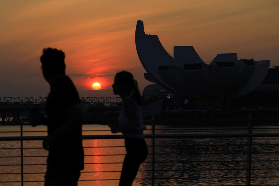 People jog along the Jubilee Bridge as the sun rises behind the ArtScience Museum at Marina Bay on February 15, 2021 in Singapore.  (Photo by Suhaimi Abdullah/NurPhoto via Getty Images)