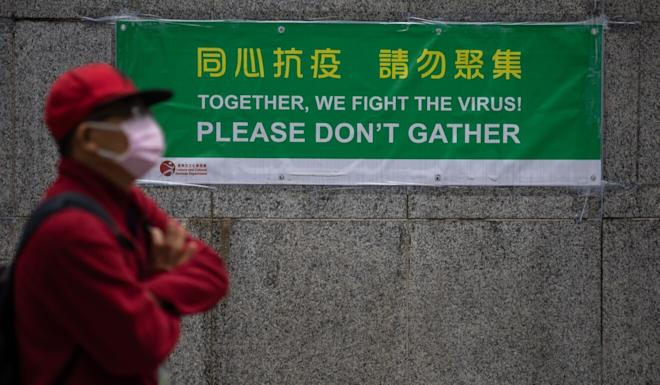 A man in a mask walks past a sign reminding Hong Kong residents about social distancing. Photo: EPA-EFE