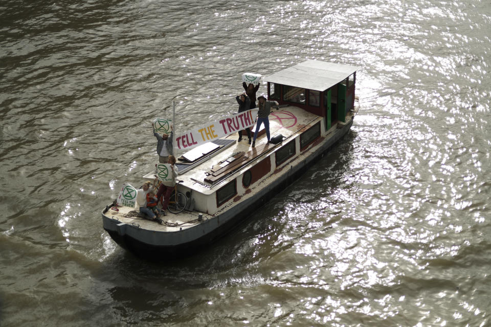 """Climate protestors on a boat with a banner reading """"Tell the Truth"""" pass Britain's Parliament in central London Monday, Oct. 7, 2019. Activists with the Extinction Rebellion movement blocked major roads in London, Berlin and Amsterdam on Monday at the beginning of what was billed as a wide-ranging series of protests demanding new climate policies. (AP Photo/Matt Dunham)"""