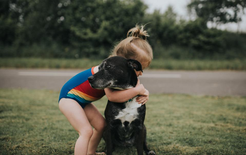Cute young girl hugs black dog.