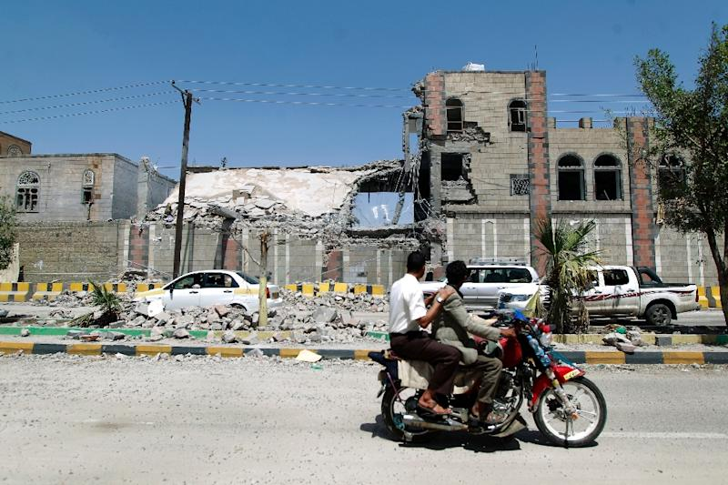 Yemenis ride their motorbike past the rubble of a building following an air-strike by the Saudi-led coalition in the capital Sanaa on June 8, 2015 (AFP Photo/Mohammed Huwais)