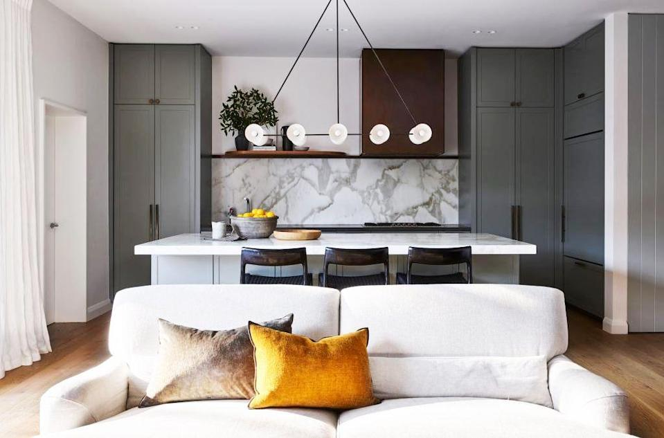 <p>There's a lot to love about this kitchen designed by Arent & Pyke, but we're particularly impressed by the careful, asymmetrical balance happening here. The hood leans to the right of the room, as do the bar stools, which is subtlety reflected in the cream lumbar pillow camouflaging into the sofa. Meanwhile, the linear floating shelf in line with the hood as well as the light fixture, island counter, and sofa form a soothing sense of symmetry. </p>