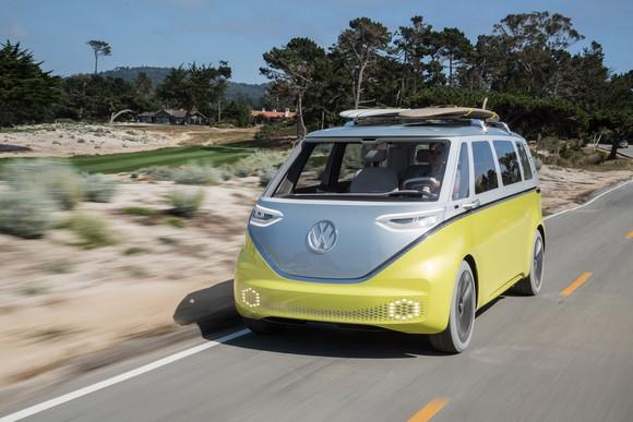 The VW I.D. Buzz show vehicle, a silver and yellow van styled after the 1960s VW Microbus, is shown driving on a beach road in California. There are two surfboards on the vehicle's roof.