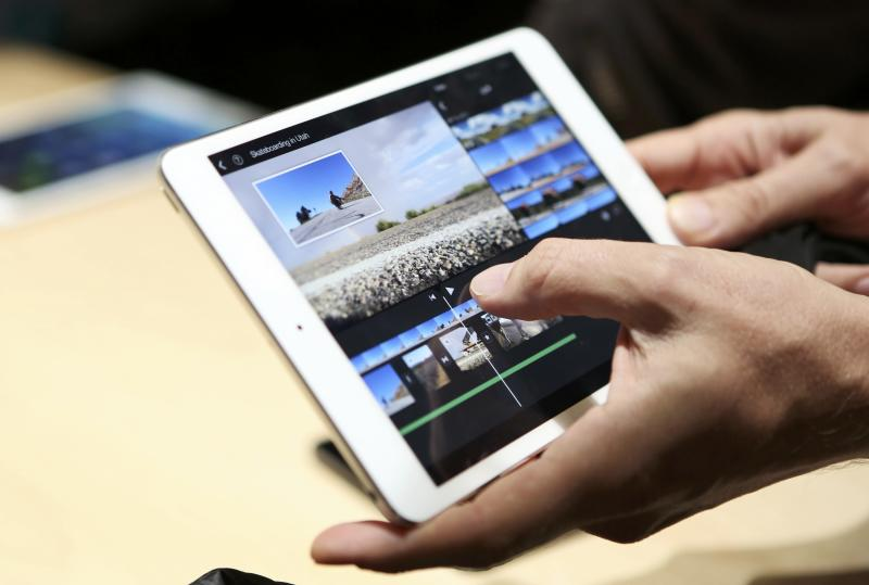 A member of the media holds the new iPad mini with Retnia display during an Apple event in San Francisco, California October 22, 2013. REUTERS/Robert Galbraith (UNITED STATES - Tags: BUSINESS TELECOMS SCIENCE TECHNOLOGY)