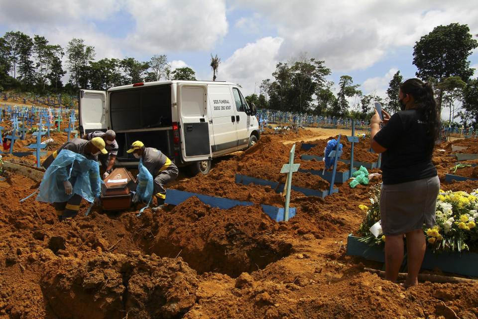 A relative films as cemetery workers remove the coffin of 89-year-old Abilio Ribeiro, who died of the new coronavirus, from a funeral service vehicle to his grave at the Nossa Senhora Aparecida cemetery in Manaus, Amazonas state, Brazil, Wednesday, Jan. 6, 2021. (AP Photo/Edmar Barros)