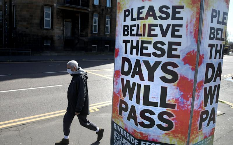 A person walks passed a billboard poster outside Glasgow Royal Infirmary as the UK continues in lockdown to help curb the spread of the coronavirus.