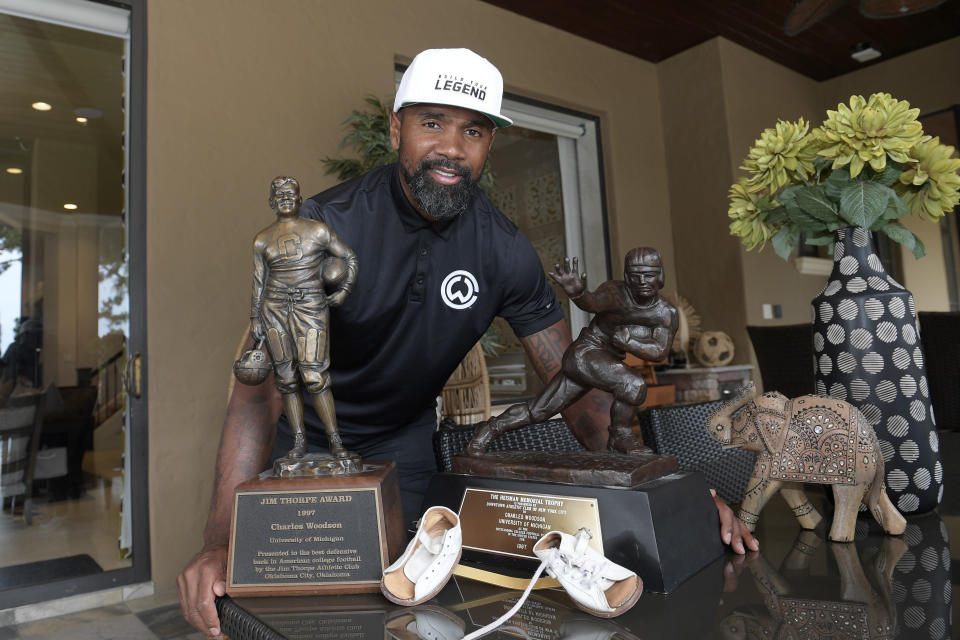 Former NFL football player Charles Woodson poses next to his collegiate Jim Thorpe Award, Heisman Trophy and clubfoot brace shoes, while reflecting on his life and career as he prepares for induction into the NFL Hall of Fame, during an interview at his home Tuesday, June 15, 2021, in Orlando, Fla. (AP Photo/Phelan M. Ebenhack)