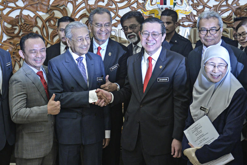 Prime Minister Tun Dr Mahathir Mohamad shakes hands with Finance Minister Lim Guan Eng in Parliament October 11, 2019, after the tabling of Budget 2020. — Picture by Shafwan Zaidon