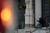 A man wearing a protective mask points his guns outside the Cathedral Church of St. John the Divine in the Manhattan borough of New York City