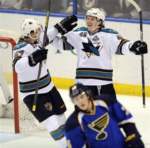 San Jose Sharks' Tim Kennedy (46) celebrates his winning goal with Tommy Wingles (57) as St. Louis Blues' T.J. Oshie skates away in the third period of an NHL hockey game, Tuesday, Feb. 19, 2013, in St. Louis. The Sharks won 2-1. (AP Photo/Bill Boyce)