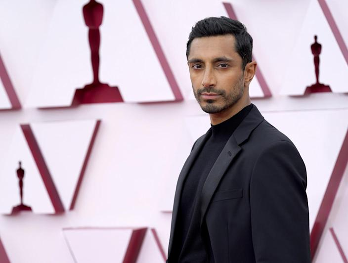 Riz Ahmed in a black suit over a black shirt.