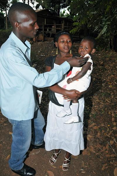 In this photo of Friday, Aug. 16, 2013, Michael Mubangizi, left, his wife Jennifer, centre, with their baby at their home in Kyebando a suburb of Uganda's capital Kampala. When their twin children were presented to them at Mulago Hospital, one baby was healthy and the other cold and lifeless, a sight made them believe one of their twin babies had been swapped. They rejected the dead one, and months later the results of a DNA test proved they were right. A Ugandan court is set to hear his case against the top public hospital whose staff face persistent complaints of negligence _and even cruelty _ in the treatment of mothers who give birth there. (AP Photo / Stephen Wandera)
