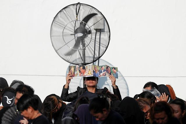 <p>Mourners shield themselves from the sun as they wait for the Royal Cremation ceremony of Thailand's late King Bhumibol Adulyadej to begin near the Grand Palace in Bangkok, Thailand, Oct. 26, 2017. (Photo: Damir Sagolj/Reuters) </p>