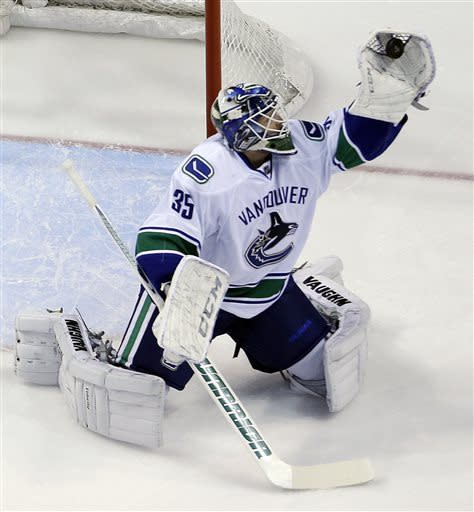 Vancouver Canucks goalie Cory Schneider makes a glove save during the first period of an NHL hockey game against the St. Louis Blues Tuesday, April 16, 2013, in St. Louis. (AP Photo/Jeff Roberson)