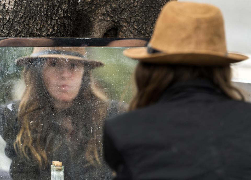 """Dawn Woodward, 39, who is homeless and originally from Arizona, checks herself in the mirror set outdoors in a homeless camp on the side of the CA-101 highway in the Echo Park neighborhood in Los Angeles Tuesday, May 11, 2021. California Gov. Gavin Newsom on Tuesday proposed $12 billion in new funding to get more people experiencing homelessness in the state into housing and to """"functionally end family homelessness"""" within five years. (AP Photo/Damian Dovarganes)"""