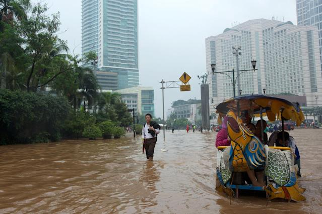 JAKARTA, INDONESIA - JANUARY 17: People wade through floodwaters in Jakarta's central business district on January 17, 2013 in Jakarta, Indonesia. Thousands of Indonesians were displaced and the capital was covered in many key areas in over a meter of water after days of heavy rain. (Photo by Ed Wray/Getty Images)