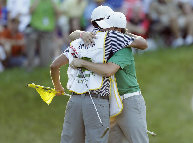 Jordan Spieth hugs his caddie Michael Greller, left, after winning the John Deere Classic golf tournament, Sunday, July 14, 2013, at TPC Deere Run in Silvis, Ill. Spieth defeated Zach Johnson and David Hearn in a 5-hole sudden death playoff. (AP Photo/Charlie Neibergall)
