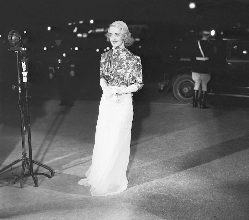 <p>Bette Davis poses at the 1932 Hollywood premiere of <em>The Man Who Played God.</em></p>