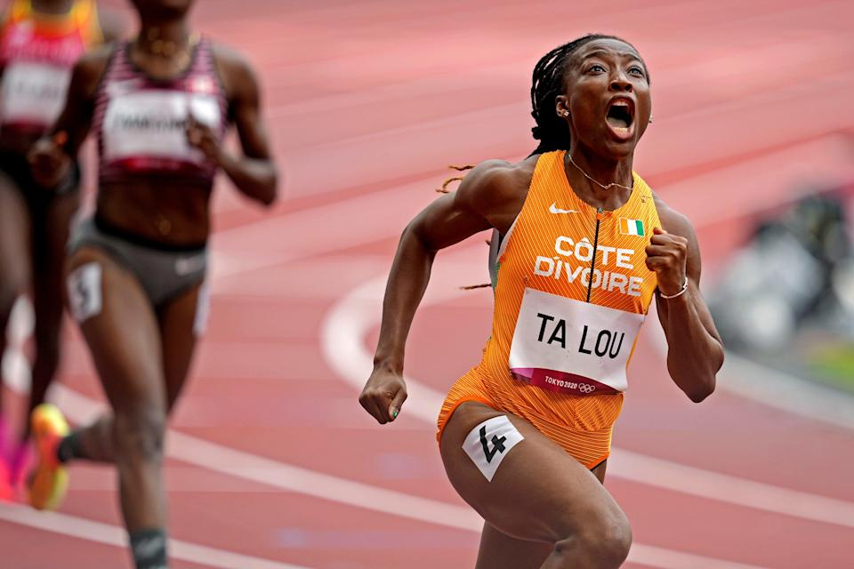Marie-Josee Ta Lou of the Ivory Coast reacts after finishing her heat of the 100-meter dash at Olympic Stadium.