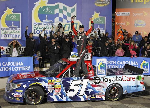 Kyle Busch celebrates in Victory Lane after winning the NASCAR Trucks series auto race at Charlotte Motor Speedway in Concord, N.C., Friday, May 16, 2014. (AP Photo/Terry Renna)