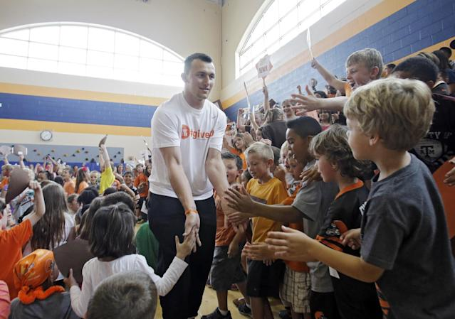 Cleveland Browns rookie quarterback Johnny Manziel is greeted by students at Grindstone Elementary school in Berea, Ohio Wednesday, June 4, 2014. The Browns 2014 rookies visited the school to kick off the NFL football team's community volunteer initiative. (AP Photo/Mark Duncan)