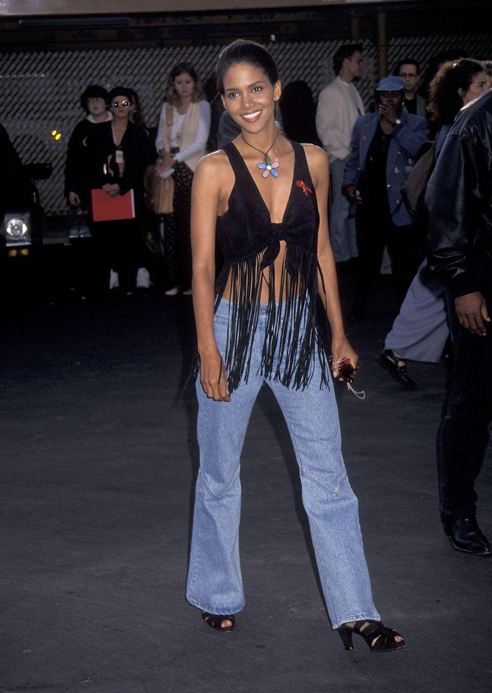<p>At the MTV Movie Awards, Halle opted to wear a bra top with extra-long fringe, bootcut jeans, and a giant flower choker. </p>