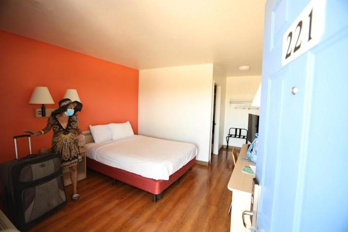 WHITTIER, CA - JULY 07, 2020 - - Genia Hope, 52, moves into her new room at a hotel that is being used for Project Roomkey in Whittier on July 7, 2020. Hope had been living homeless in an encampment near the 710 and 105 freeways for the past two years. Outreach workers with the Los Angeles Housing convinced Hope to move into the hotel. Project Roomkey is a coordinated effort to secure hotel and motel rooms in L.A. County as temporary shelters for people experiencing homelessness who are at high-risk for hospitalization if they contract Coronavirus (COVID-19). The city and county of Los Angeles plan to move people from the freeways. U.S. District Judge David O. Carter passed a landmark court order banning homeless encampments from under and along Los Angeles freeways. (Genaro Molina / Los Angeles Times)
