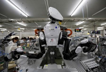 FILE PHOTO: A humanoid robot works side by side with employees in the assembly line at a factory of Glory Ltd., a manufacturer of automatic change dispensers, in Kazo, north of Tokyo