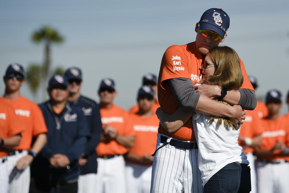 Associate coach Nate Johnson, left, embraces his wife Jonai during a ceremony held for John Altobelli, the late head coach of Orange Coast College baseball, who died in a helicopter crash alongside former NBA basketball player Kobe Bryant in Costa Mesa, Calif., Tuesday, Jan. 28, 2020. His wife Keri and youngest daughter Alyssa were also victims of the crash. (AP Photo/Kelvin Kuo)
