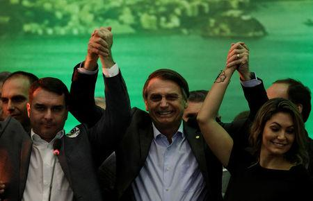 Federal deputy Jair Bolsonaro holds his hands up with his son Flavio Bolsonaro (L) and his wife Michelle Bolsonaro during the national convention of the Party for Socialism and Liberation (PSL) where he is to be formalised as a candidate for the Presidency of the Republic, in Rio de Janeiro, Brazil July 22, 2018. REUTERS/Ricardo Moraes