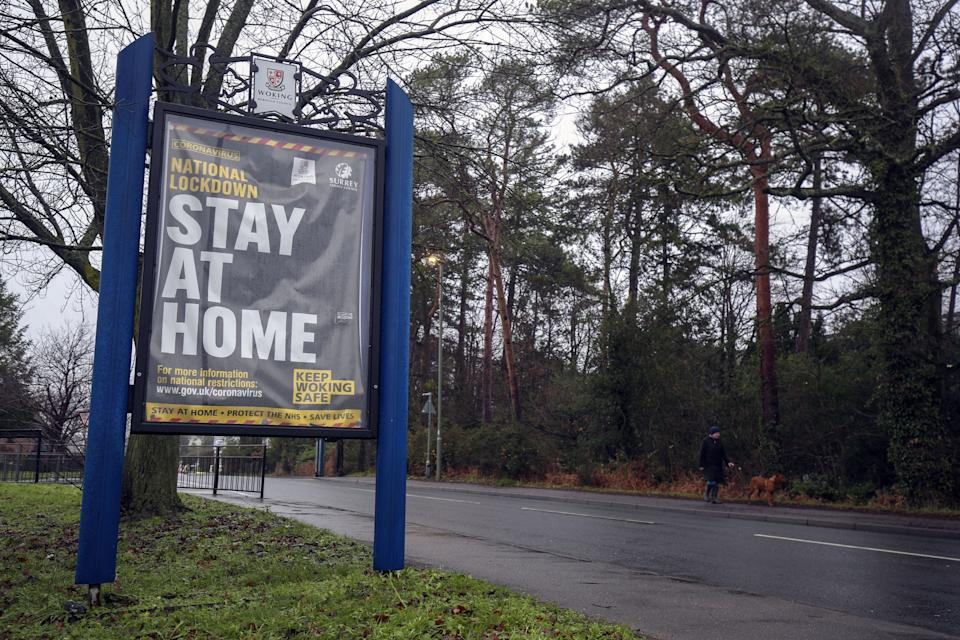 A person walks past a coronavirus information sign in Brookwood, Surrey, during England's third national lockdown to curb the spread of coronavirus. Picture date: Wednesday January 27, 2021.
