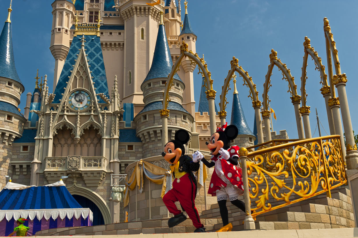 Mickey Mouse and Minnie Mouse perform in front of the Cinderella Castle, Magic Kingdom, Walt Disney World, Orlando, Florida USA