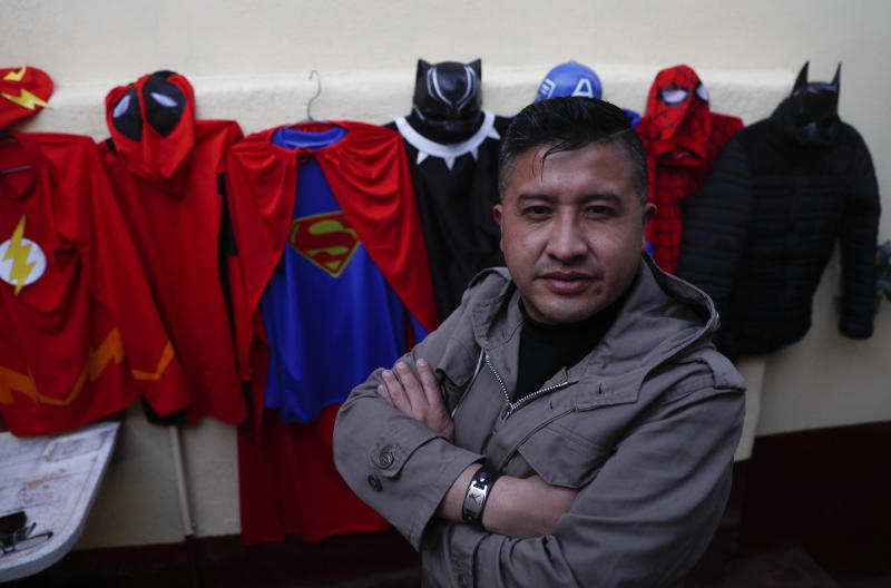 """Art teacher Jorge Manolo Villarroel poses for a photo next to his superhero costumes, after imparting one of his online classes from his home, amid the new coronavirus pandemic in La Paz, Bolivia, Tuesday, June 10, 2020. Villarroel makes the costumes he wears. """"I had to improvise since with the quarantine I couldn't get out,"""" he said. (AP Photo/Juan Karita)"""