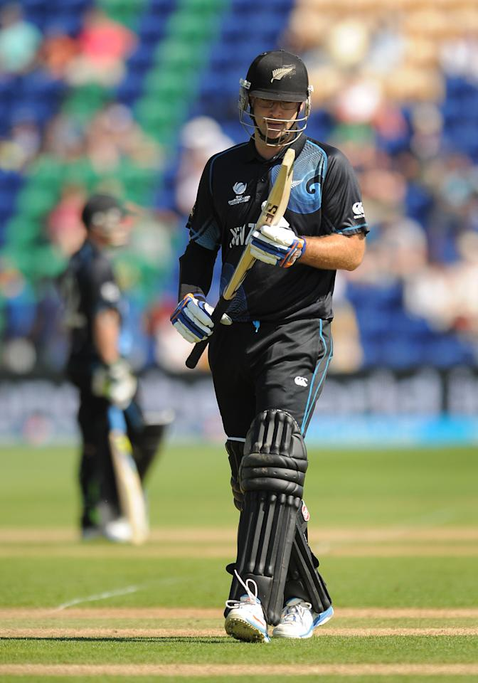 New Zealand's Daniel Vettori looks at his bat as he walks off the field of play after losing his wicket during the ICC Champions Trophy match at the SWALEC Stadium, Cardiff.