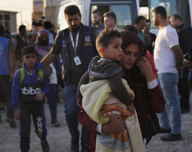 A Syrian woman who is newly displaced by the Turkish military operation in northeastern Syria, carries her son upon her arrival at the Bardarash camp, north of Mosul, Iraq, Wednesday, Oct. 16, 2019. The camp used to host Iraqis displaced from Mosul during the fight against the Islamic State group and was closed two years ago. The U.N. says more around 160,000 Syrians have been displaced since the Turkish operation started last week, most of them internally in Syria. (AP Photo/Hussein Malla)