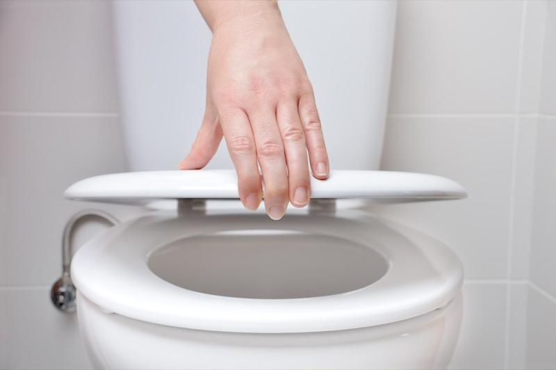 hand of a woman closing the lid of a toilet