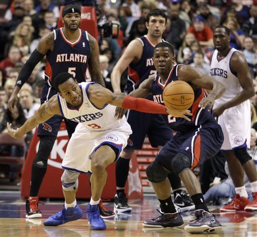Atlanta Hawks' Joe Johnson, front right, and Philadelphia 76ers' Andre Iguodala reach for a loose ball in the first half of an NBA basketball game on Saturday, March 31, 2012, in Philadelphia. (AP Photo/Matt Slocum)