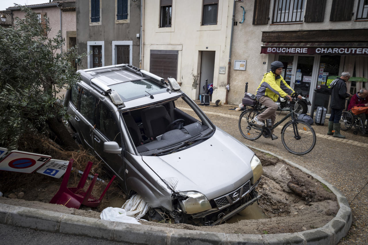 <p>A man rides past a damaged car in the town of Villegailhenc, southern France, Monday, Oct. 15, 2018. (Photo: Fred Lancelot/AP) </p>